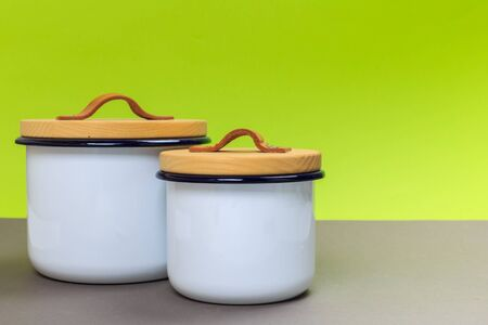 Two new metal saucepans with wooden lids on a gray table and a green background. space for text Stock Photo