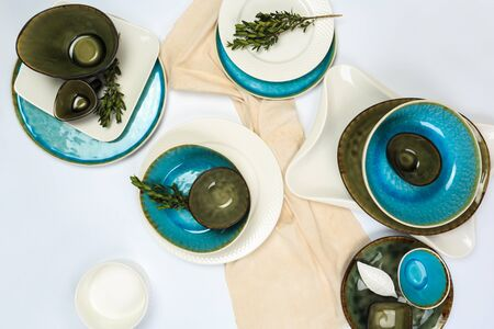 Simple rustic handmade blue crockery against white wooden wall: dish, stack of bowls.
