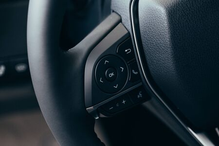 close up Modern black steering wheel with multifunction buttons Integrated stereo controls pushes the for quick control technology in the car. Standard-Bild