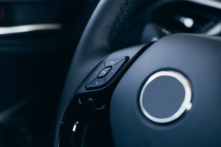 close up Modern black steering wheel with multifunction buttons Integrated stereo controls pushes the for quick control technology in the car. 版權商用圖片