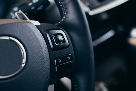 close up Modern black steering wheel with multifunction buttons Integrated stereo controls pushes the for quick control technology in the car.