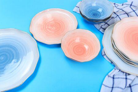 Platos y cuencos de cerámica multicolor sobre fondo azul.