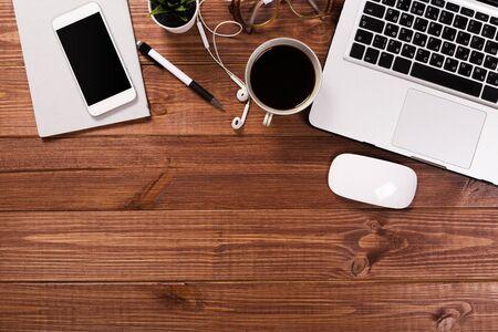 cosas de oficina con bloc de notas, ordenador portátil y taza de café, ratón, bloc de notas, vista superior, tiro. Foto de archivo