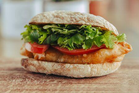 жареная рыба на булочке с листьями салата, томатная уличная еда