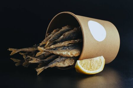 grilled sea fish with lemon wedges street food in box