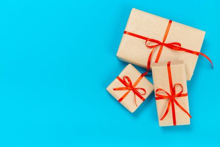 beautiful gift boxes wrapped in paper with a red ribbon and a bow on a blue surface. Top view