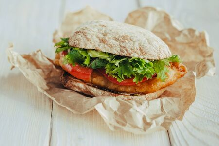 fried fish on a bun with lettuce, tomato street food