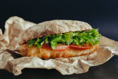 fried fish on a bun with lettuce, tomato street food Stockfoto - 129197164