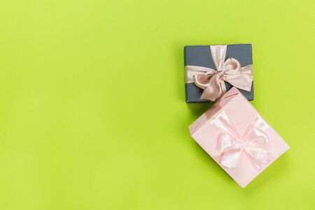 Gift box wrapped in pastel  paper with pink ribbon on green surface. Top view