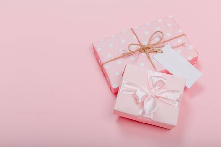 Gift box wrapped in pastel  paper with pink ribbon on pink surface. Top view Фото со стока