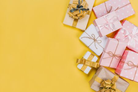 beautiful gift boxes wrapped in paper with red, gold and pink ribbon on a yellow surface. Top view