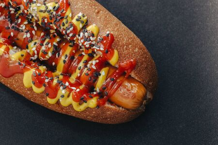 Big hotdog with sausage tomatoes, mustard and salad isolated on black background. Top view. Stockfoto - 129198231