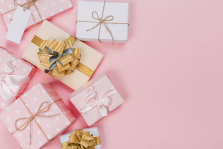 Gift box wrapped in pastel  paper with pink and gold  ribbon on pink surface. Top view