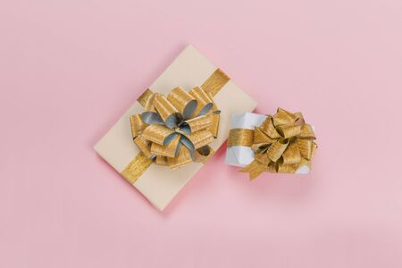 Gift box wrapped in pastel  paper with gold  ribbon on black surface. Top view