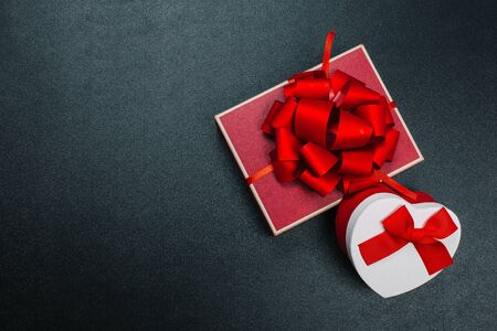 Gift box wrapped in  paper with red ribbon on black surface. Top view Фото со стока