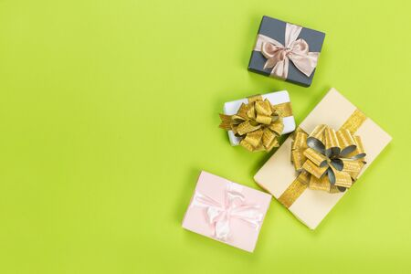 Gift box wrapped in pastel  paper with pink and gold  ribbon on green surface. Top view
