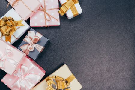 beautiful gift boxes wrapped in paper with red, gold and pink ribbon on a black surface. Top view Фото со стока