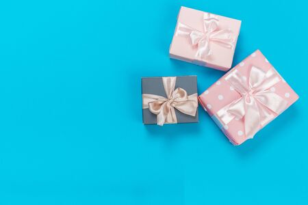 beautiful gift boxes wrapped in paper with gold and pink ribbon on a blue surface. Top view with copy space.