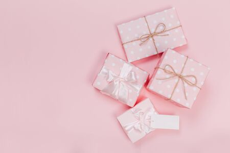 Gift box wrapped in pastel  paper with pink ribbon on pink surface. Top view Reklamní fotografie