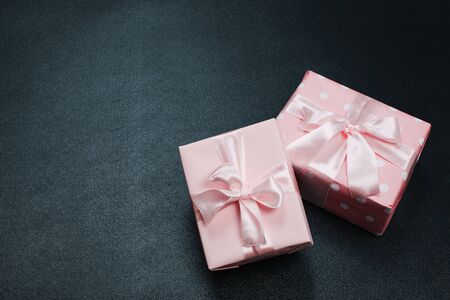 beautiful gift boxes wrapped in paper with red, gold and pink ribbon on a black surface. Top view Banco de Imagens - 129376364