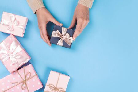 Womans hands holding gift or present box on blue pastel table top view. Flat lay  for birthday or New Year.