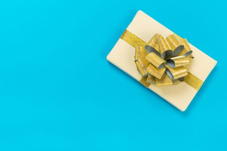 beautiful gift box wrapped in paper with a gold ribbon and a bow on a blue surface.