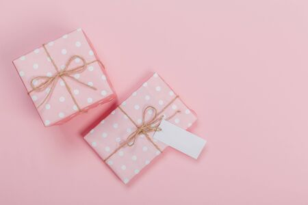 Gift box wrapped in pastel  paper with pink ribbon on pink surface. Top view Banco de Imagens - 129376583