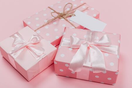 Gift box wrapped in pastel  paper with pink ribbon on pink surface. Top view Banco de Imagens - 129376497