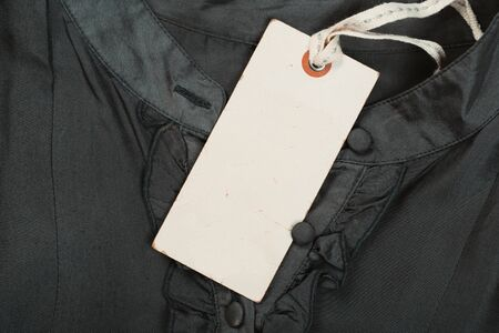 Rectangular Tag on a clothes. fashion, people and shopping concept - close up price tag of clothing item Banco de Imagens