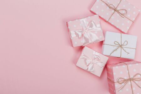 Gift box wrapped in pastel  paper with pink ribbon on pink surface. Top view Banco de Imagens