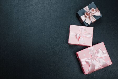 beautiful gift boxes wrapped in paper with red, gold and pink ribbon on a black surface. Top view Banco de Imagens