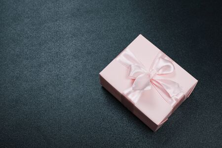 Gift box wrapped in pastel  paper with pink ribbon on black surface. Top view