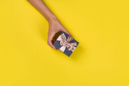 Womans hands holding gift or present box on Yellow table top view. Flat lay  for birthday or New Year. Banco de Imagens - 129376296