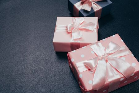 beautiful gift boxes wrapped in paper with red, gold and pink ribbon on a black surface. Top view Reklamní fotografie