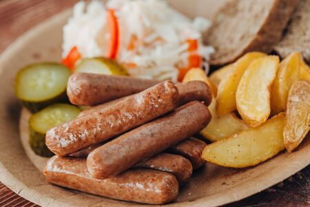 Tasty sausages with fried potatoes, cucumber, cabbage and chlobe in a paper plate on a wooden table. takeaway street food