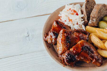 Pyszne smażone skrzydełka z kurczaka z sosem, smażonymi ziemniakami, ogórkiem, kapustą i klobe w papierowym talerzu na drewnianym stole. uliczne jedzenie
