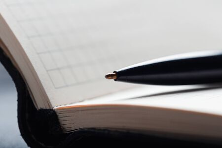 Opened notepad with automatic plastic ballpoint pen close up.