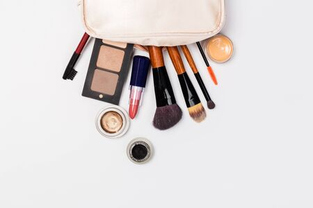 Makeup brush and decorative cosmetics on a white background. Top view Фото со стока
