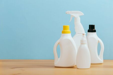 Cleaning product plastic container for house clean on wooden table and blue background .  household chemicals Stockfoto