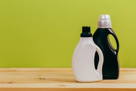 Cleaning product plastic container for house clean on wooden table and green background .  household chemicals