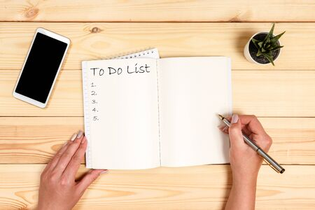 To do list Concept - 2020 number and text on notepad. Modern workspace with smartphone, paper, notebook and female hands on wooden background. Stockfoto