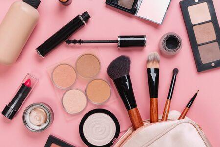 Set aus dekorativem Kosmetikpuder, Concealer, Lidschattenpinsel, Rouge, Foundation auf rosa Hintergrund