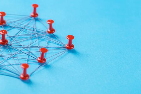 network with red and white pins and string, An arrangement of colorful pins linked together with string on a blue background suggesting a network of connections. Stock Photo