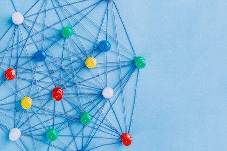 Small network of pins (Thumbtack)and string, An arrangement of colorful pins linked together with string on a pale blue background suggesting a network of connections. 版權商用圖片