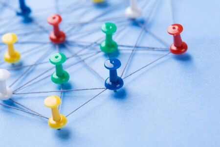 Small network of pins (Thumbtack)and string, An arrangement of colorful pins linked together with string on a pale blue background suggesting a network of connections. Stock Photo