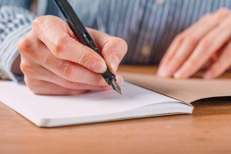 Le belle mani femminili scrivono la penna in un taccuino di compiti e obiettivi per lavorare su un tavolo