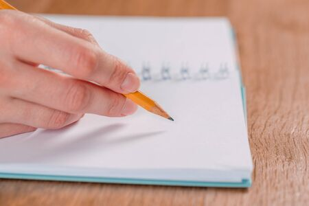 Close up of womans hands writing in spiral notepad placed on wooden desktop