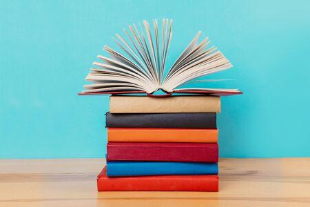 Una semplice composizione di molti libri con copertina rigida, libri grezzi su un tavolo di legno e uno sfondo blu brillante. Tornare a scuola. Copia spazio. Formazione scolastica.