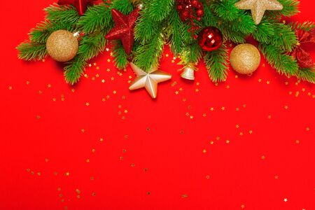 Christmas red background with herringbone and decor. Gold and red jewelry. Top view with space for copy.