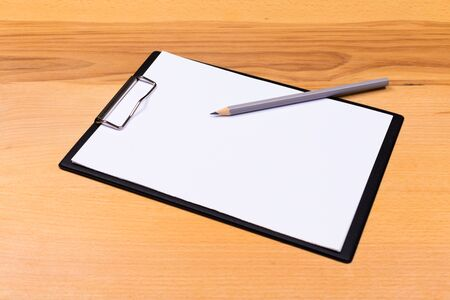 Blank paper with pen on wooden clipboard with space on background